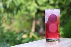 Jugo frío, rosado con hielo en una taza de cristal en un de madera en el fondo verde del jardín Foto de archivo