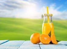 Jugo fresco con la fruta anaranjada en la tabla de madera Fotos de archivo