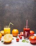 Jugo fresco de las comidas sanas en vidrios con la paja, naranjas y frontera de los tomates, con la opinión superior del fondo rú Foto de archivo libre de regalías