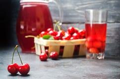 Jugo o compota con las cerezas Cereza roja madura fresca en una cesta en un fondo concreto gris, baya del verano, espacio para el fotografía de archivo