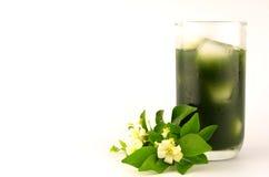 Jugo vagetable verde con el jazmín anaranjado Fotografía de archivo libre de regalías