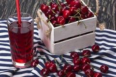 Jugo y cerezas rojas en una caja de madera Fotografía de archivo