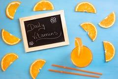 Jugo y rebanadas anaranjadas como diariamente vitaminas Imágenes de archivo libres de regalías