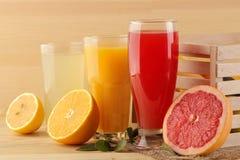 Jugos de la fruta cítrica jugo de la naranja, del limón y de pomelo con las frutas frescas en una caja en un fondo de madera natu imagenes de archivo