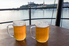 Jugs of beer placed on a wooden table on background river Danube and Bratislava castle, Slovakia. Two glass of beer on the brown wooden table, Slovakia royalty free stock photo