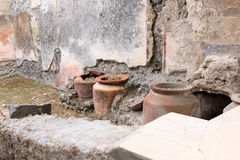 Jugs in Casa del frutteto in Roman Pompeii, Italy. The city of Pompeii was an ancient Roman town-city near modern Naples. Pompeii along with Herculaneum and many royalty free stock photo
