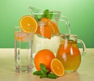 Jugs with drinks, glass and oranges Royalty Free Stock Photography