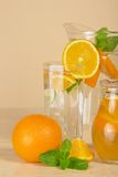 Jugs with drinks, oranges and spearmint Royalty Free Stock Photography