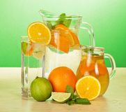 Jugs and glass with oranges juicy Stock Photos