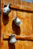 Jugs & pitcher. Ancient pitcher and jugs hanging on the wooden door Stock Photo