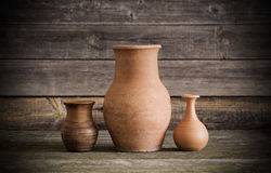 Jugs on wooden background Stock Photos