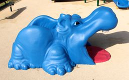 Juguete azul y rojo colorido del hipopótamo en el patio de los niños Fotos de archivo libres de regalías