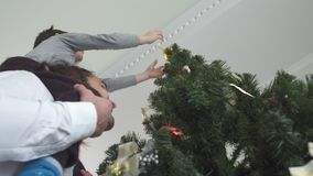 Juguete colgante de la Navidad del niño alegre en el árbol que se sienta en su cuello del padre Relación del padre y del hijo metrajes