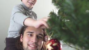Juguete colgante de la Navidad del niño feliz en el árbol que se sienta en su cuello del padre Relación del padre y del hijo almacen de metraje de vídeo