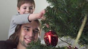 Juguete colgante de la Navidad del niño pequeño en el árbol que se sienta en su cuello del padre Relación del padre y del hijo metrajes