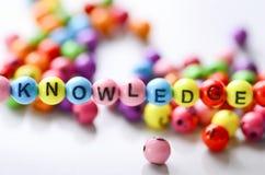 Juguete colorido del alfabeto con un conocimiento de la palabra en él Fotografía de archivo libre de regalías