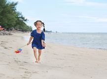 Juguete colorido y funcionamiento del molino de viento del control del bebé en la playa por la tarde fotos de archivo libres de regalías