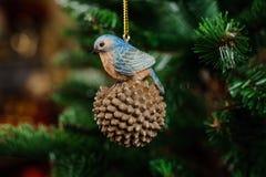 Juguete de la decoración del árbol de navidad bajo la forma de pájaro que se sienta en el cono de abeto Fotografía de archivo