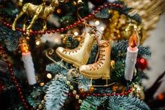 Juguete de la decoración del árbol de navidad bajo la forma de patines de oro Imagen de archivo