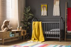 Juguete de la felpa en armario de madera al lado de la cama gris con el blanke amarillo fotos de archivo libres de regalías
