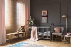Juguete de la felpa en armario de madera al lado de la cuna gris en el ` s del niño más allá imagen de archivo
