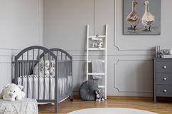 Juguete de la felpa en taburete delante de la cama gris en el interior del dormitorio del niño con la escalera y el cartel Foto v imagen de archivo