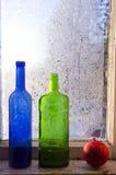 Juguete de la Navidad del Año Nuevo y botella vieja dos en ventana del invierno con helada Fotografía de archivo libre de regalías