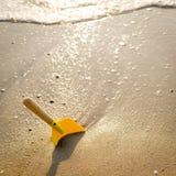 Juguete de la playa: paleta amarilla en la playa foto de archivo