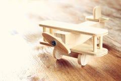 Juguete de madera del aeroplano sobre fondo de madera texturizado Imagen retra del estilo Foto de archivo