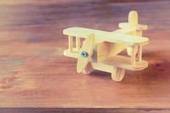 Juguete de madera del aeroplano sobre fondo de madera texturizado Imagen retra del estilo Imagen de archivo libre de regalías