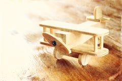 Juguete de madera del aeroplano sobre fondo de madera texturizado Imagen retra del estilo Imagen de archivo