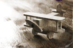 Juguete de madera del aeroplano sobre fondo de madera texturizado Imagen retra del estilo foto blanco y negro del viejo estilo Fotografía de archivo