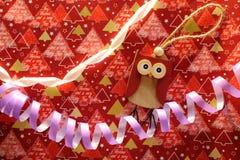 Juguete de madera del búho y serpantine violeta con la cinta blanca en el abrigo festivo como decoración de la Navidad y del Año  Fotografía de archivo