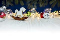 Juguete de madera del caballo y bolas de cristal en fondo borroso con el abeto Imagen de archivo