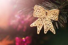 Juguete de oro del arco en un árbol de navidad Fotografía de archivo