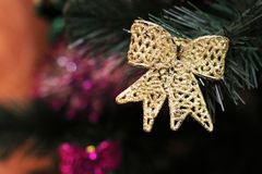 Juguete de oro del arco en un árbol de navidad Foto de archivo libre de regalías