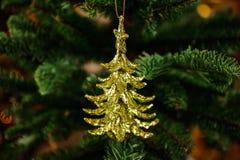 Juguete de oro de la decoración del árbol de navidad bajo la forma de poco árbol de abeto Imagen de archivo libre de regalías