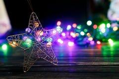 Juguete de oro de la estrella de la Navidad en fondo del ligh colorido de la guirnalda Foto de archivo libre de regalías