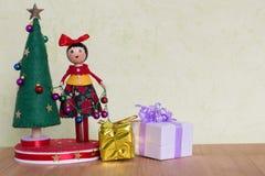 Juguete del árbol de navidad con una señora que adorna con las bolas, los regalos y los muñecos de nieve coloridos Foto de archivo