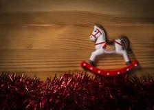 Juguete del caballo mecedora sobre fondo de madera de la textura con la guirnalda brillante Imágenes de archivo libres de regalías