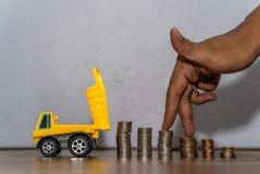Juguete del camión volquete que transfiere una pila de las monedas, mano como finger que corre en el montón de monedas Fotos de archivo