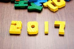 juguete del color del amarillo del número del Año Nuevo 2017 en la tabla de madera con la otra f Imágenes de archivo libres de regalías