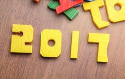 juguete del color del amarillo del número del Año Nuevo 2017 en la tabla de madera con la otra f Foto de archivo
