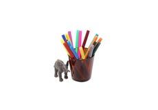 Juguete del elefante y lápices coloreados en un vidrio Imagen de archivo libre de regalías