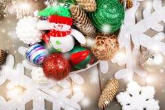 Juguete del muñeco de nieve en cesta con las bolas de la Navidad Efectos mágicos ligeros, nieve de dibujo Fotos de archivo libres de regalías