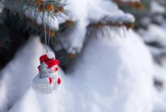 Juguete del muñeco de nieve en una picea Imagenes de archivo