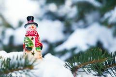 Juguete del muñeco de nieve en una picea Fotos de archivo