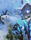 Juguete del oso polar de la Navidad en la nieve con las luces Imágenes de archivo libres de regalías