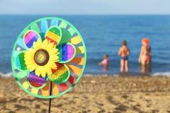 Juguete del Pinwheel en la playa, familia que se coloca en agua Foto de archivo libre de regalías