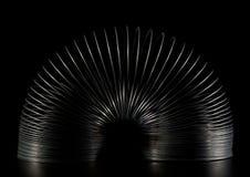 Juguete del resorte furtivo en negro Imagenes de archivo